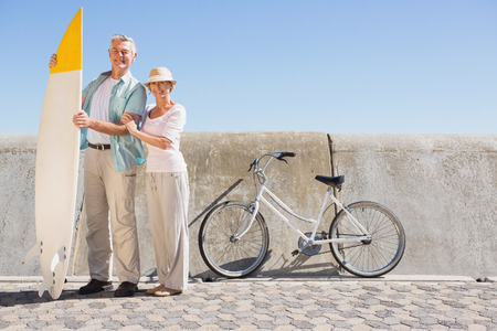 Happy senior couple posing with surfboard on a sunny day photo