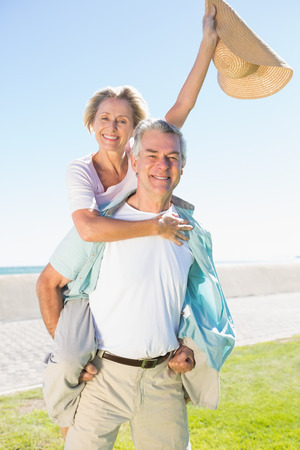 escapism: Happy senior man giving his partner a piggy back on a sunny day