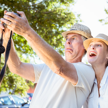 Happy senior couple posing for a selfie on a sunny day photo