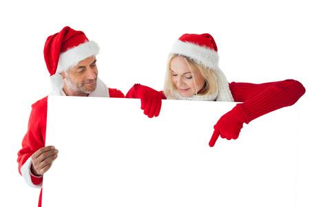Festive couple pointing to large white card on white background photo