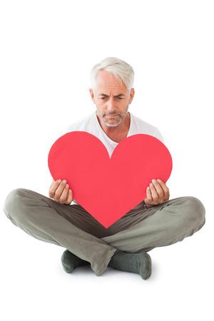 lonesomeness: Upset man sitting holding heart shape on white background Stock Photo