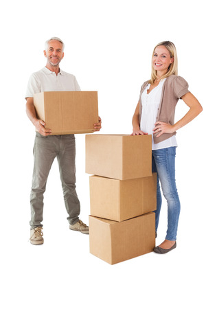Happy couple smiling at camera with moving boxes on white background photo