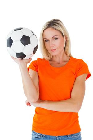 unsmiling: Football fan holding ball in orange tshirt on white background Stock Photo