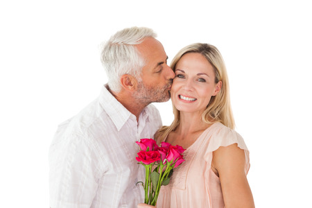 Affectionate man kissing his wife on the cheek with roses on white background photo