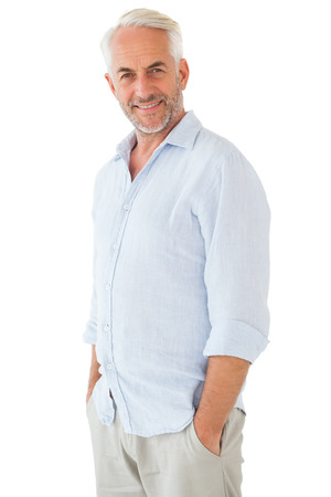 chinos: Smiling man posing with hands in pockets on white background