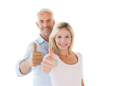 Smiling couple showing thumbs up together on white background