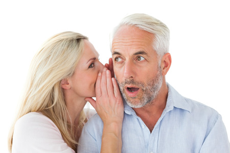 Woman whispering a secret to husband on white background photo
