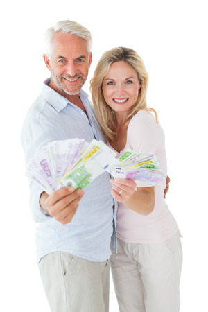 Happy couple flashing their cash on white background photo