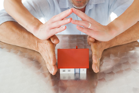 sheltering: Couple sheltering miniature house with hands on white background