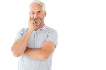 Smiling man posing with arms crossed on white background photo