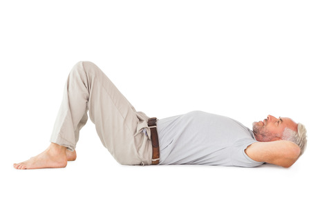 chinos: Smiling man lying and looking up on white background
