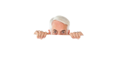wide eyed: Wide eyed man showing large poster on white background