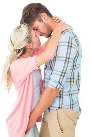 Attractive young couple about to kiss on white background photo