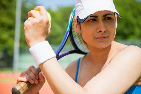 Pretty tennis player sitting on court on a sunny day photo