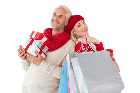 Smiling couple in winter fashion holding presents and shopping bags on white background photo