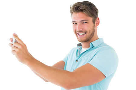 Handsome young man taking photo with smartphone on white background photo