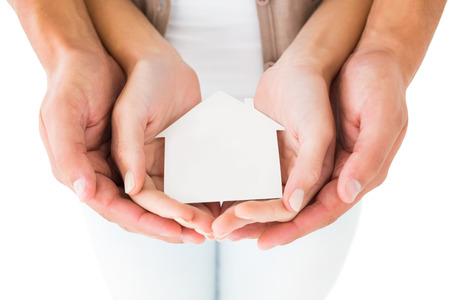 Couple holding miniature house in hands on white background photo
