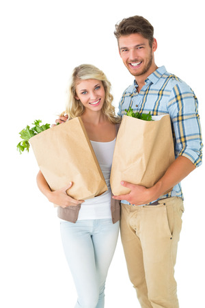 Attractive couple holding their grocery bags on white background photo