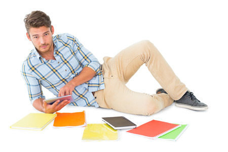 chinos: Handsome young man lying and studying on white background