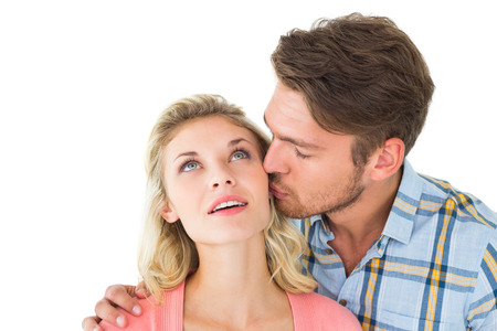 Handsome man kissing girlfriend on cheek on white background photo