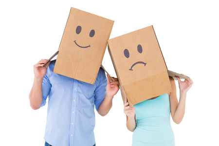 Couple wearing sad face boxes on their heads on white background