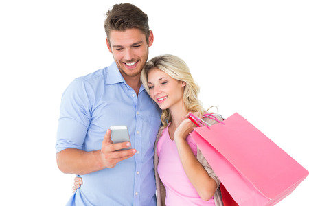 Attractive young couple holding shopping bags looking at smartphone on white background photo