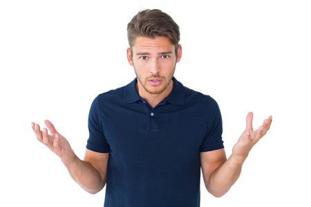 Handsome young man shrugging shoulders on white background photo
