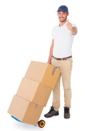 Happy delivery man pushing trolley of boxes on white background photo