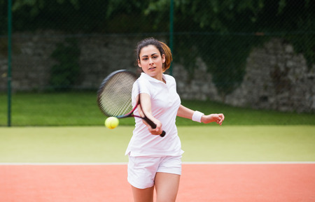 Young tennis player hitting ball on a sunny day photo