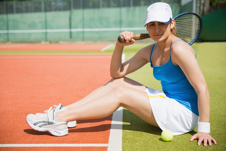 Pretty tennis player sitting on court smiling at camera on a sunny day photo