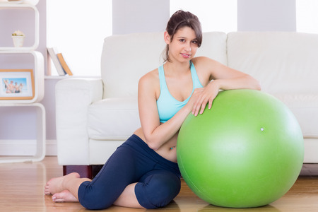 Fit brunette leaning on exercise ball smiling at camera at home in the living room photo