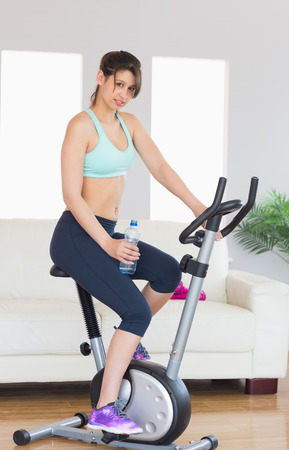 Fit brunette working out on exercise bike at home in the living room photo