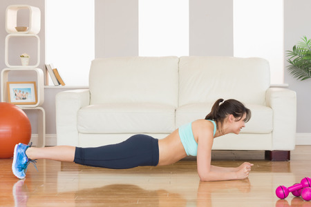plank position: Fit brunette in plank position at home in the living room
