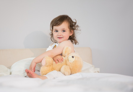 Portrait of a cute little girl sitting on bed at home photo