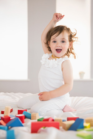 Portrait of a cute happy girl playing with building blocks on bed at home photo