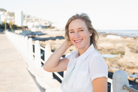 off path: Casual woman smiling at camera by the sea  on a sunny day Stock Photo