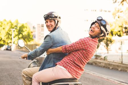 晴れた日に市内でスクーターに乗って幸せな熟年カップル 写真素材