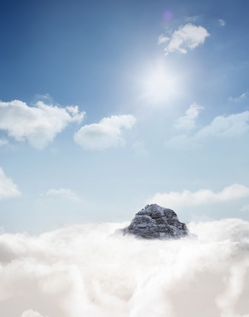 Digitally generated Mountain peak through the clouds Stock Photo