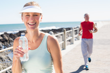 fair woman: Fit mature couple jogging together on the pier on a sunny day Stock Photo