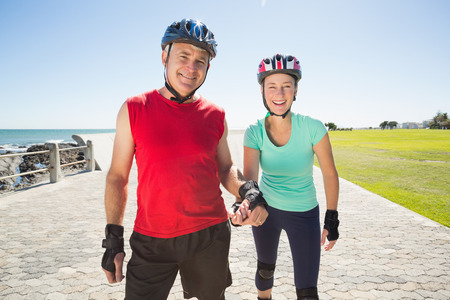 off path: Fit mature couple rollerblading on the pier on a sunny day Stock Photo
