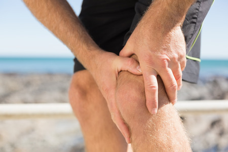 injured knee: Fit man gripping his injured knee on a sunny day