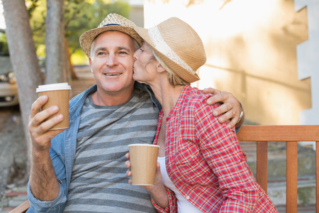 hot drink: Happy mature couple drinking coffee on a bench in the city on a sunny day