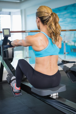 Rear view of a young woman working on fitness machine at the gym Stock Photo