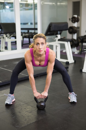 Full length of a serious young woman lifting kettle bell in the gym Stock Photo