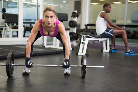 Portrait of a fit young woman lifting barbell in the gym photo