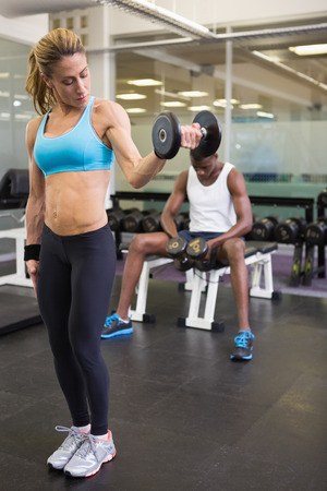 Full length of a fit young woman exercising with dumbbell in the gym photo
