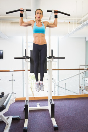 Full length of a young fit woman doing crossfit fitness workout in gym Stock Photo