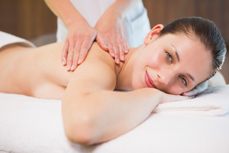 Side view portrait of an attractive young woman receiving back massage at spa center photo