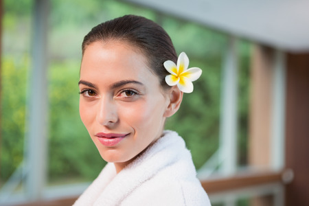 Portrait of a beautiful young woman in bathrobe against blurred plants photo