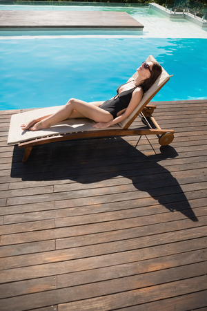 Side view of beautiful young woman in bikini relaxing by swimming pool photo